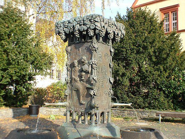 Dieses Kunstwerk an der Mosel steht in Bernkastel-Kues. Der Doctorbrunnen. Er zeigt reliefartig die Geschichte des berühmten Bernkasteler Doctorweins.